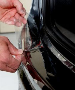 Cleargard Technician Removes Protective Wrap From Car Rear