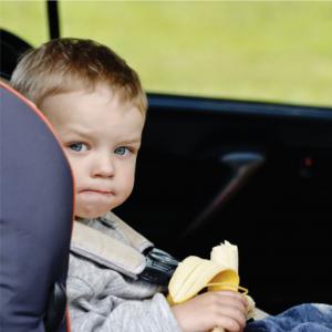 Child Eating Banana In Car Seat