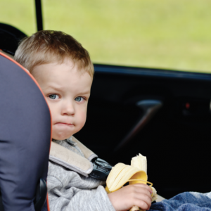 Kid With Banana In Car Seat