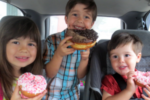 Children Eating Donuts In The Car